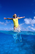 Woman jumping into sea, caught by camera half in half out of the water. Tonga