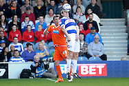 Queens Park Rangers Richard Dunne competes with Blackpool's Kevin Foley. Skybet football league championship match , Queens Park Rangers v Blackpool at Loftus Road in London  on Saturday 29th March 2014.<br /> pic by John Fletcher, Andrew Orchard sports photography.