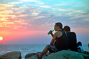 two young adults drinking beer during sun set