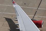 Aerial view (from control tower) of Virgin Atlantic airliner's wing and engine at London Heathrow airport.