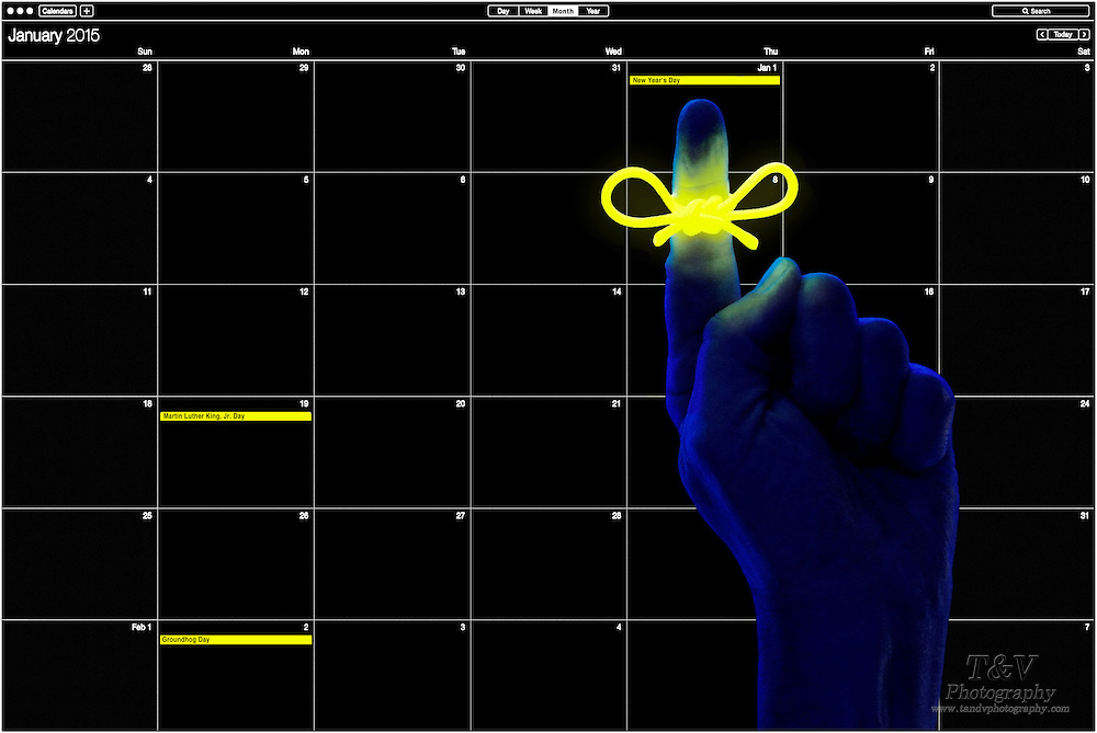 A glowing reminder string on the index finger of a darkly lit blue hand point to January 1st on a 2015 calendar.Black light