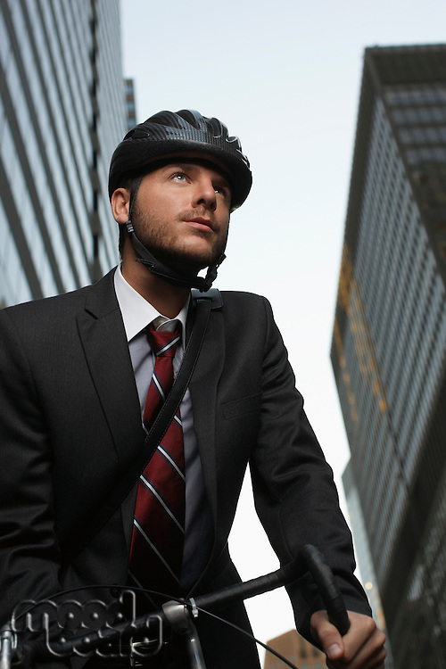 Man standing by bicycle in street low angle view