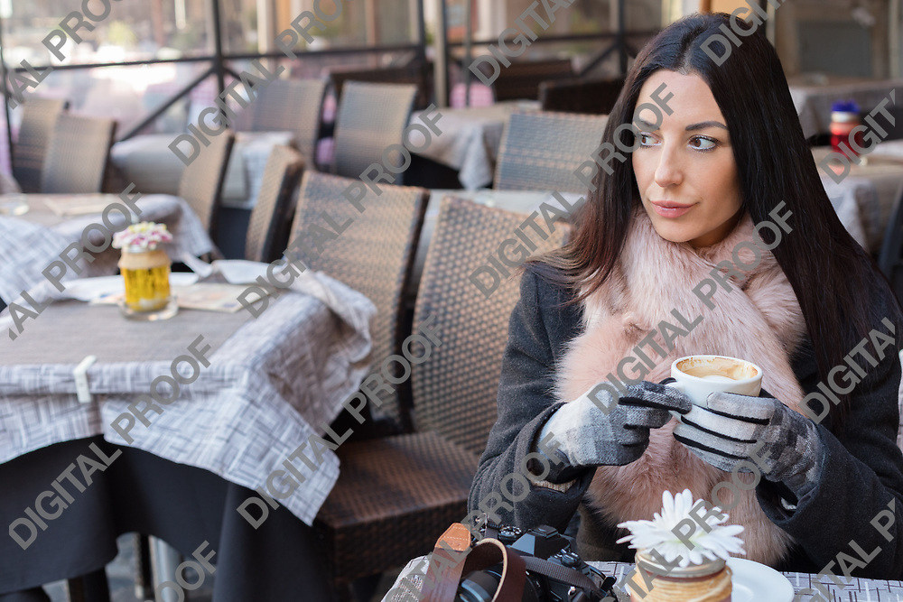 Pensive, beautiful and elegant woman sitting on an european cafe