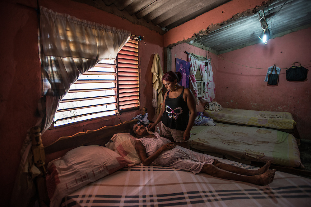 """LA VELA, VENEZUELA - SEPTEMBER 11, 2016: Maria Piñero takes care of her elderly mother, Felipa Palencia de Piñero, who is diabetic. The family struggles to find the medicine that she needs. To escape the crisis, Ms. Piñero spent all of her savings to pay smugglers to take her in a small fishing boat to Curacao island. """"I'm nervous,"""" she said. """"I'm leaving with nothing. But I have to do this. Otherwise, we will just die here hungry."""" Another benefit of living and working in Curacao, she said, is that she will be able to find and pay for her mother's medicines, and ship them to her in Venezuela.  Despite having the largest known oil reserves in the world, Venezuela is suffering from hyperinflation and a severe economic crisis making affordable food difficult for most middle and working class families to access.  Well over 150,000 Venezuelans have fled the country in the last year alone, the highest in more than a decade, according to scholars studying the exodus. As Hugo Chávez's Socialist-inspired revolution collapses into economic ruin, as food and medicine slip further out of reach, the new migrants include the same impoverished people that Venezuela's policies were supposed to help. """"We have seen a great acceleration,"""" said Tomás Paez, a professor who studies immigration at the Central University of Venezuela. He says that as many as 200,000 Venezuelans have left in the last year, driven by how much harder it is to get food, work and medicine — not to mention the crime such scarcities have fueled.  PHOTO: Meridith Kohut for The New York Times"""