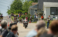 With spectators lining Tower Hill Road riders race up during the Tower Hill Climb at Weirs Beach on Tuesday. (Karen Bobotas/for the Laconia Daily Sun)