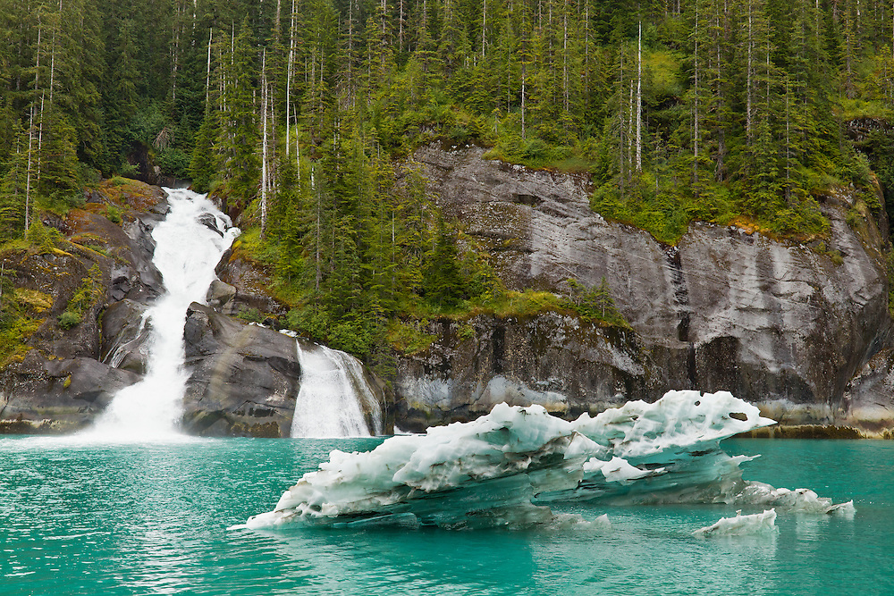 An iceberg from South Sawyer Glacier floats in front of an unnamed waterfall in Tracy Arm fjord (Tracy Arm - Fords Terror Wilderness) in the Inside Passage of Southeast Alaska. Summer. Afternoon.