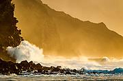 Ocean waves crash against cliffs on the rugged Na Pali Coast , with the light of the setting sun. Kauai, Hawaii, © 2010 David A. Ponton