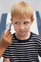 Boy having temperature taken with ear thermometer
