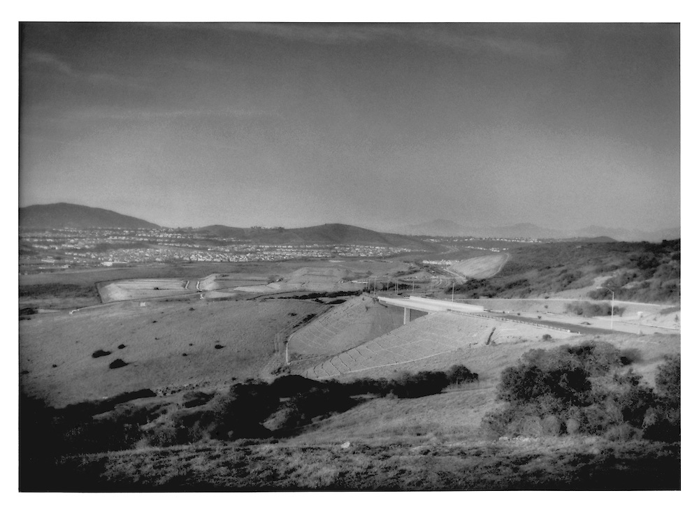 Great change to the landscape as infrastructure literally will pave the way to make possible the conversation from agricultural land to suburban housing development, below Black Mountain, northern San Diego County, California, USA.
