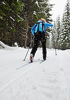 A low angle view of a woman cross country skiing in the classic style on a groomed course at Cabin Creek Snow Park, WA, USA.