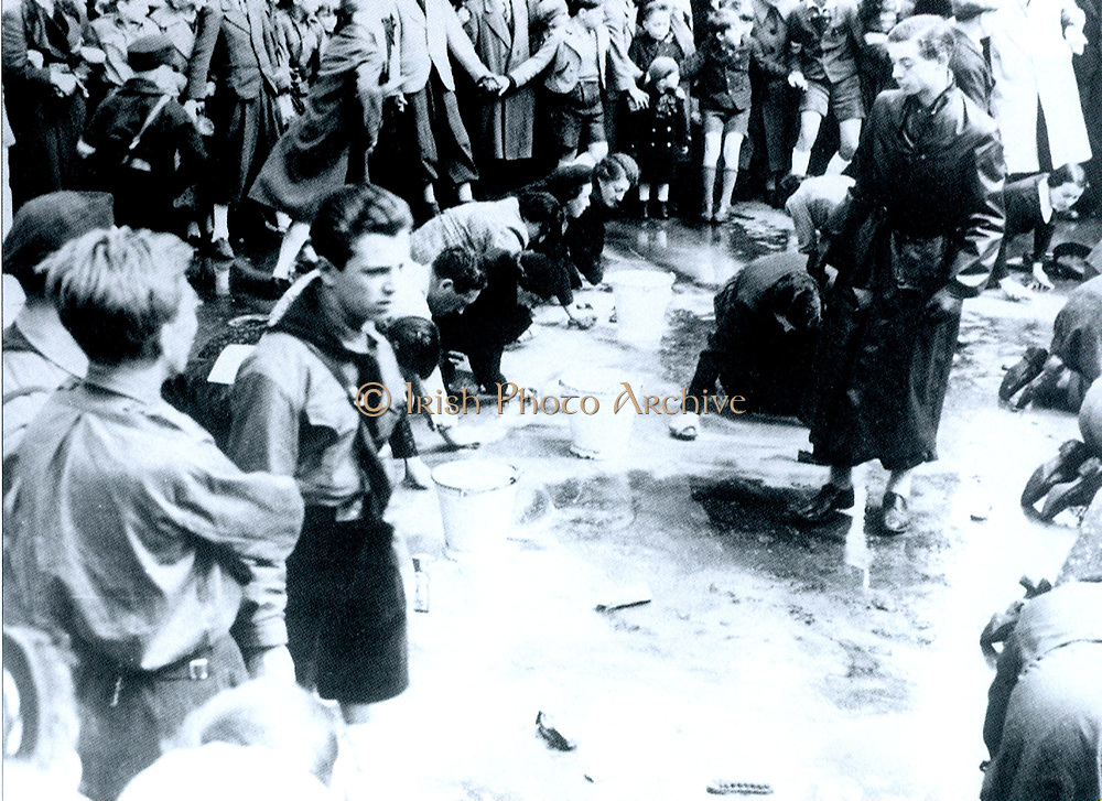 Austrian Jews forced to wash a street in Vienna following the German Anschluss (Annexation) of Austria in 1938