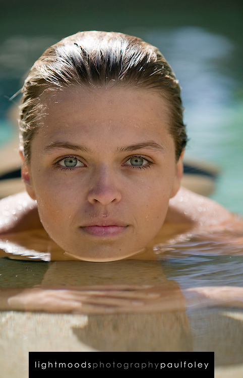 Beautiful Woman in pool, looking at camera