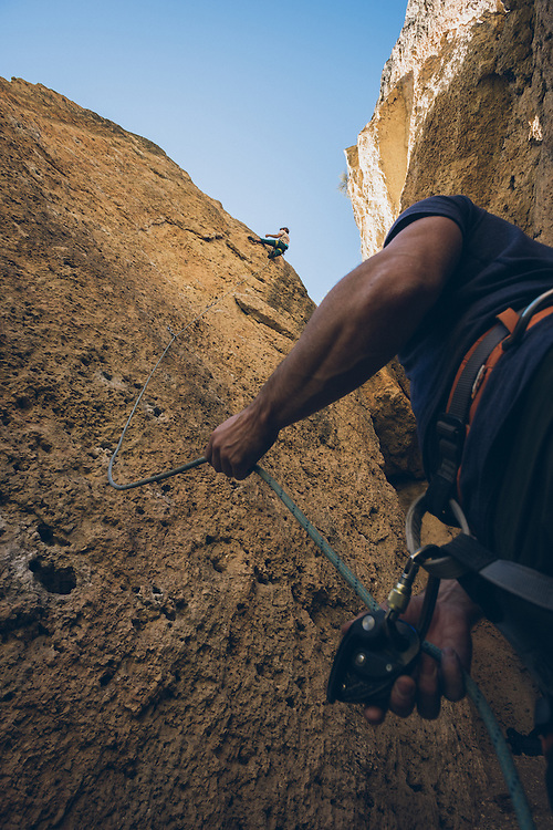 Colin O'Brien reaching the chains at the top of 'Plea Bargain' (5.10a) in Ten Sleep Canyon, WY