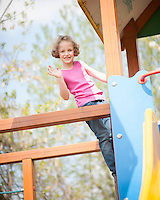 Young girl climbing on childrens playground and waving at camera