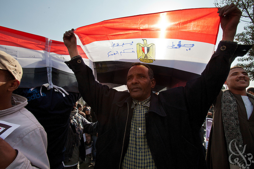 Egyptian activists chant anti-military slogans and wave flags and posters with similar messages during a January 20, 2012 protest march outside the Mustafa Mahmoud mosque in Cairo, Egypt. The hundred or so protestors marched on Tahrir square to join larger crowds there, and similar marches took place across Cairo with the intent on building momentum before next week's one year anniversary of the revolution.(Photo by Scott Nelson)