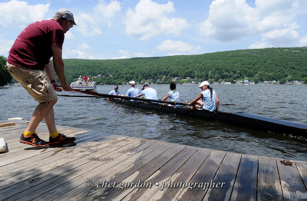GREENWOOD LAKE, NY.  An all-woman team of rowers drift to a dock after their race during the 15th. Annual Greenwood Lake Spring Regatta in Greenwood Lake, NY on Sunday, June 2, 2013.   © Chet Gordon/THE IMAGE WORKS