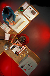 Stock photo of an overhead view of two men working at a table