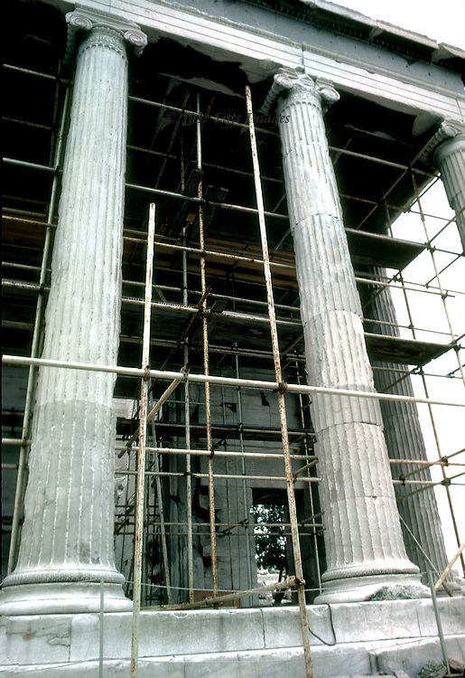 Two of the exquisitely perfect Ionic columns of the Erechtheum on the Athens Acropolis, scaffolding behind them in preparation for restoring the temple.