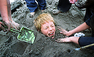 Elric Neumann, 10, gets coverd by sand by his fellow classmates from Treasure Island School while taking a break from building a sand castle during the 17th Annual Sand Castle Classic held on Ocean Beach near the Cliff House. .Examiner/Jakub Mosur...October 7, 2000