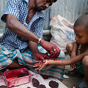 A small boy is having his hand and arm painted with henna using small precut symbols. The painting is done by a man who travels the slums and small back streets of Dhaka charging small money to do the painting. His customers are usually children. This boys is having his paiting paid for by his his father.