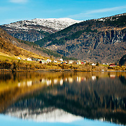 Mountains and houses reflect in the waters of Granvinsvatnet lake, near the village of Granvin, also known as Eide in Norway.
