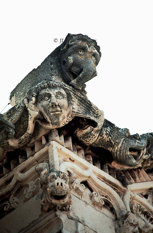Sculptured heads include an elephant, a man, a dog, and a fish (?) on the corner of a cornice.
