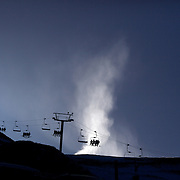 The chair lift in operation on the opening day of Coronet Peak Ski Field as snow making equipment continues to make snow. .Unusually warm weather which included New Zealand experiencing its hottest May since record-keeping began caused long delays to the start of the ski season and the region has yet to receive a snow fall of any significance. Snow making equipment and a recent cold spell has allowed enough time for the ski field to finally open almost four weeks late.  Coronet Peak, Queenstown,  South Island, New Zealand, 30th June 2011