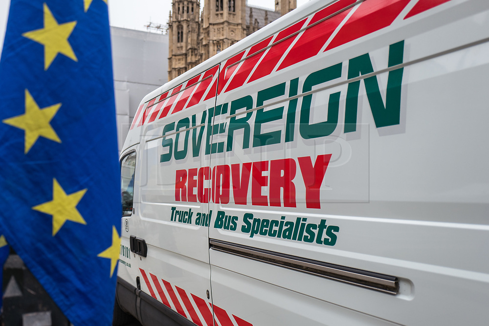 © Licensed to London News Pictures. 14/11/2017. London, UK. A recovery van which reads 'SOVEREIGN RECOVERY' pulls up alongside anti-Brexit protesters as they demonstrate outside Parliament while MPs debate the European Union (Withdrawal) Bill. Photo credit: Rob Pinney/LNP