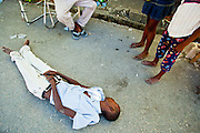 18 NOVEMBER 2010 - PORT-AU-PRINCE, HAITI:  A dead body at a bus stop in front of a MSF cholera stabilization center in Cite Soliel in Port-au-Prince. People in Cite Soleil are afraid of cholera and there is a stigma to the disease because no one wants be accused of bringing it into the community. People at the bus stop said the man didn't die of cholera, but they didn't know why he had died. They said he suddenly got sick and died, symptoms of cholera. Cite Soleil, a sprawling slum area in PAP is ground zero for the cholera epidemic in the Haitian capital. An outbreak of cholera in northern Haiti about a month ago has spread across the nation. Tens of thousands of people have been hospitalized and treated for cholera and more than 1,100 have died. Cholera is a water borne illness that causes severe diarrhea and death by dehydration in a matter of hours.    PHOTO BY JACK KURTZ  choleraepidemic