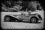 Westbury, New York, USA. June 12, 2016.  MARK OFFENBERG, of Valley Stream, drives his silver 1973 Intermeccanica Squire SS-100 Italian  luxury classic roadster while his passenger holds 3rd Place Trophy the car won in the foreign car category at the Antique and Collectible Auto Show at the 50th Annual Spring Meet at Old Westbury Gardens, in the Gold Coast of Long Island, and sponsored by Greater New York Region, GNYR, Antique Automobile Club of America, AACA. Car is the 46th of only 50 Intermeccanica's coachbuilt in Turin, Italy. Participating vehicles in the judged show included hundreds of domestic and foreign, antique, classic, collectible, and modern cars and trucks.