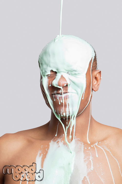 Paint falling on shirtless young Hispanic man's head against gray background