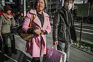 "Some well-heeled Chinese travelers on the ""bakugai"" (explosive buying) circuit of shops known to Chinese tourists in the Ginza district.  Travelers from China often come straight from the airport by bus to begin shopping.  Ginza, Tokyo, Japan."