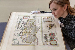 The Bonham's Scottish Sale takes place at Bonham's in Edinburgh on Wednesday 25 April at 1pm. Now in its 19th year it features works by leading Scottish artists as well as a huge range of objects related to Scotland.<br /> <br /> Pictured: A 17th century atlas of Scotland and Ireland by the famous Dutch cartographer Jan Blaeu published in 1662, and estimated at &pound;10,000-12,000. examined by Georgia Williams of Bonhams