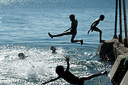 Silhouettes of children jumping and playing in the sea. Africa, Mozambique, Ilha de Mocambique.