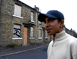 Youth hanging out in deprived area of Halifax; Yorkshire; UK, Boarded up houses in background