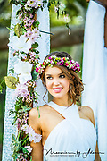 Bride by flower archway with floral hair arrangement
