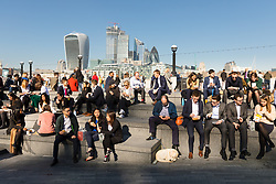 © Licensed to London News Pictures. 26/02/2019. London, UK.  Office workers eating lunch in front of City of London skyscrapers on the south bank at lunchtime during another day of unseasonably warm sunny weather in the capital. Photo credit: Vickie Flores/LNP