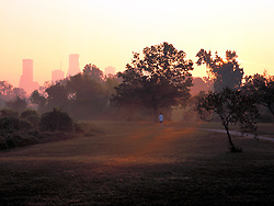 Jogger running along Buffalo Bayou Hike and Bike Trail at sunrise in Houston, Texas