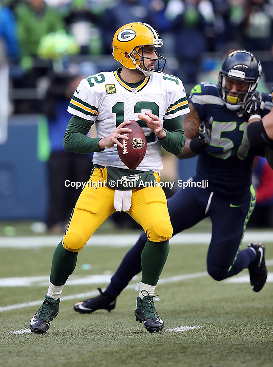 Green Bay Packers quarterback Aaron Rodgers (12) throws a third quarter pass for a first down despite pressure from Seattle Seahawks outside linebacker Bruce Irvin (51) during the NFL week 20 NFC Championship football game against the Seattle Seahawks on Sunday, Jan. 18, 2015 in Seattle. The Seahawks won the game 28-22 in overtime. ©Paul Anthony Spinelli