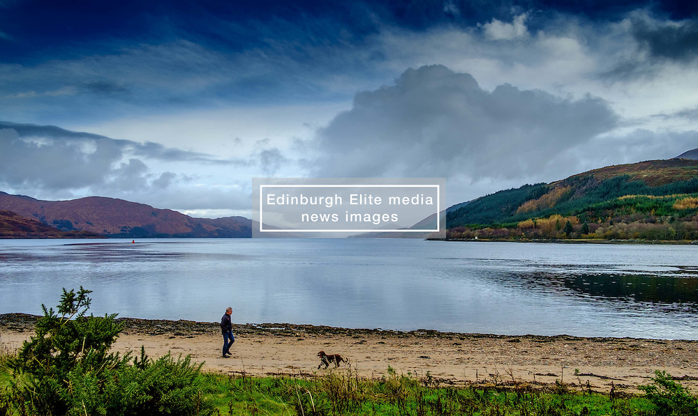 A man walks his dog on the beach at Corran Highlands of Scotland<br /> <br /> (c) Andrew Wilson | Edinburgh Elite media
