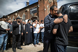 © Licensed to London News Pictures. 14/07/2017. London, UK. Brothers Bashir (L) and Hamid comfort each other after they carried the coffin of their father Mr Ali Jafari from the Hussaini Islamic Mission following funeral prayers. Mr Jafari, 82, was killed in the fire that destroyed Grenfell Tower in June. Photo credit: Peter Macdiarmid/LNP