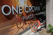 A rental Mobike leans against a tree next to an illustration of a cycling utopia at a new development called One Crown Place on Sun Street near Liverpool Street Station in the City of London, the capital's financial district - aka the Square Mile, on 8th August, in London, England.