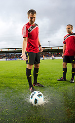 ALTACH, AUSTRIA - Saturday, July 17, 2010: Referee Ouschan Dominik tries to bounce the ball on the waterlogged pitch before Liverpool's first preseason match of the 2010/2011 season against Al-Hilal Al Saudi FC at the Cashpoint Arena. (Pic by David Rawcliffe/Propaganda)