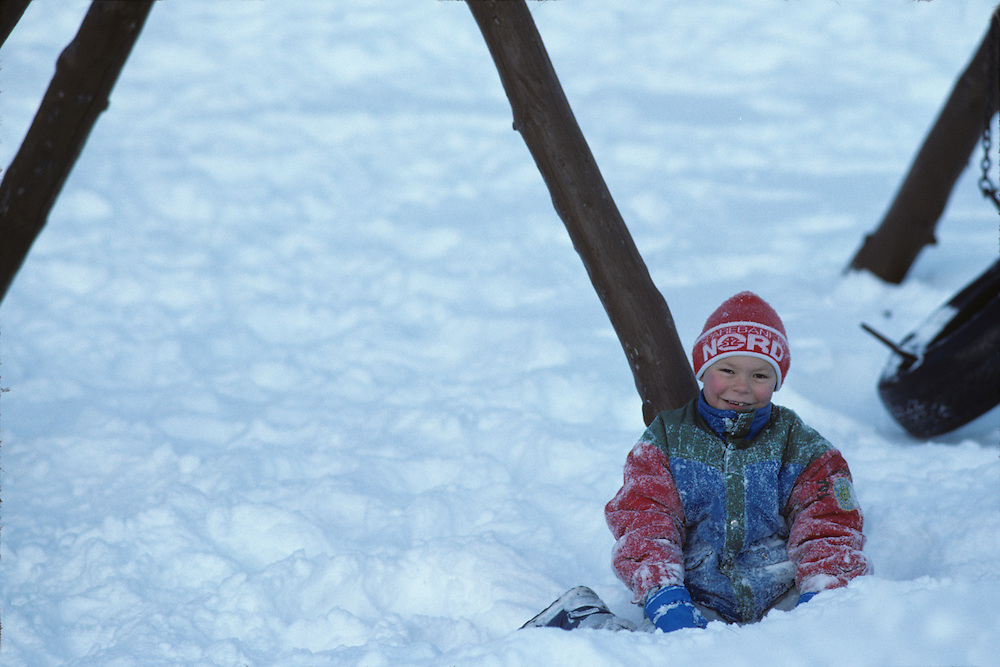 Europe, Norway, Schoolboy plays in early winter snow in arctic coast town of Kirkennes