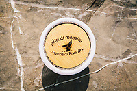 """PISCIOTTA, ITALY - 22 APRIL 2018: A terracotta container with salted Alici di Menaica (Menaica anchovies) is seen here by the harbour in Pisciotta, Italy, on April 22nd 2018.<br /> <br /> Former restaurant owners Donatella Marino and her husband Vittorio Rimbaldo have spent the recent years preparing and selling salted anchovies, called alici di menaica, to a growing market thanks to a boost in visibility from the non-profit Slow Food.  The ancient Menaica technique is named after the nets they use brought by the Greeks wherever they settled in the Mediterranean. Their process epitomizes the concept of slow food, and involves a nightly excursion with the special, loose nets that are built to catch only the larger swimmers. The fresh, red anchovies are immediately cleaned and brined seaside, then placed in terracotta pots in between layers of salt, to rest for three months before they're aged to perfection.While modern law requires them to use PVC containers for preserving, the government recently granted them permission to use up to 10 chestnut wood barrels for salting in the traditional manner. The barrels are """"washed"""" in the sea for 2-3 days before they're packed with anchovies and sea salt and set aside to cure for 90 days. The alici are then sold in round terracotta containers, evoking the traditional vessels that families once used to preserve their personal supply.<br /> <br /> Unlike conventional nets with holes of about one centimeter, the menaica, with holes of about one and half centimeters, lets smaller anchovies easily swim through. The point may be to concentrate on bigger specimens, but the net also prevents overfishing."""