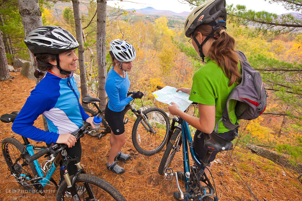 Women mountain biking on a trail on Millstone Hill in Barre, Vermont.  Abandoned granite quarry.  Fall. Millstone Trail Association. Checking map.