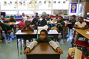 Third graders David Dobbins, center, and other students await instruction from their teacher Courtney Jackson, left, at Adelaide Davis Elementary School on Nov. 26, 2012 in Washington, D.C. Last week DCPS Chancellor Kaya Henderson proposed closing 20 under-enrolled schools in the District. Davis Elementary is one of 20 schools in the DCPS system included in the school closure proposal. There are currently 178 students enrolled in Davis Elementary and the second floor of the school is only used for music classes and the library...CREDIT: Lexey Swall for The Wall Street Journal.DCSCHOOLS