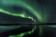 Double curtain of northern lights reflected in a fast moving region of the river. (Photo by Travel Photographer Matt Considine)