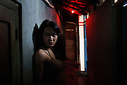 JAKARTA, INDONESIA, MARCH 2013: A young transgender stands at the entrance of the brothel in downtown Jakarta.