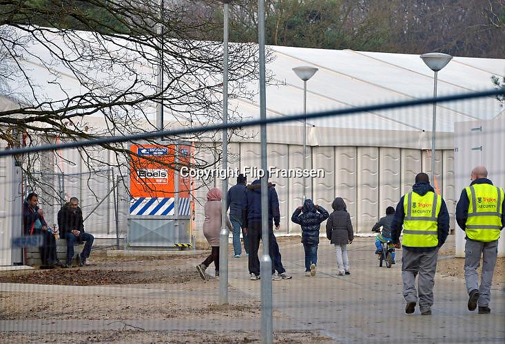 Nederland, the Netherlands, Nijmegen, 4-11-2015Kamp, tentenkamp Heumensoord, de tijdelijke noodopvang, azc, van het COA. Plaats voor 3000 asielzoekers. Mensen wandelen buiten. Door de zachte winter is het in de tenten nog niet zo koud. Beveiliging, beveiligers, security,toezicht door een particulier beveiligingsbedrijf.FOTO: FLIP FRANSSEN
